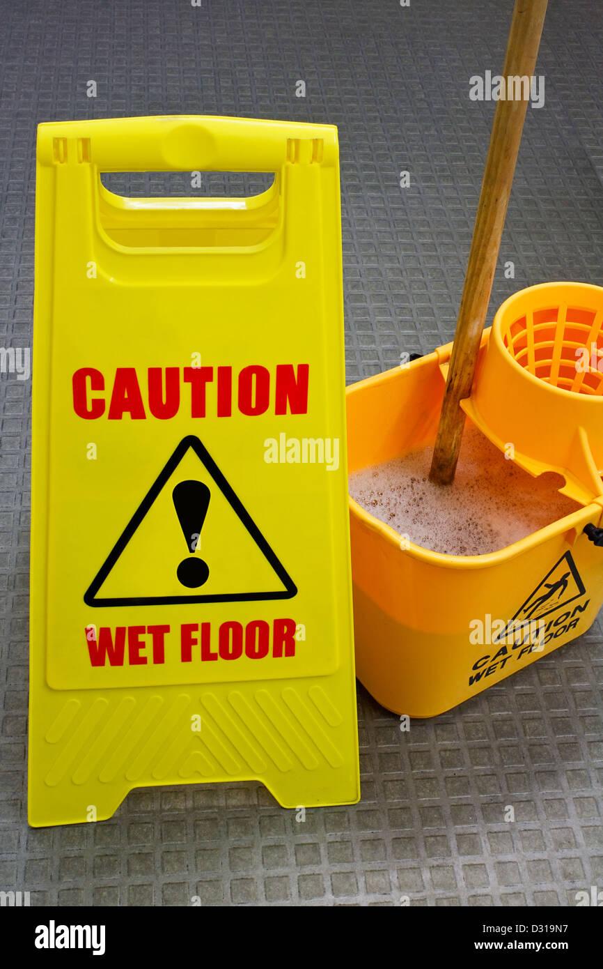Segnale di avvertimento pavimento bagnato con mop e benna Immagini Stock