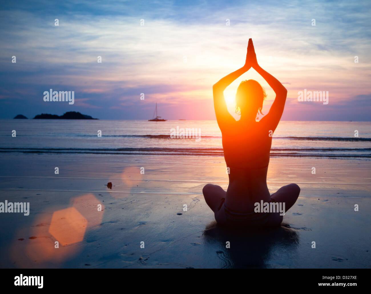 Silhouette donna giovane a praticare yoga sulla spiaggia al tramonto. Immagini Stock