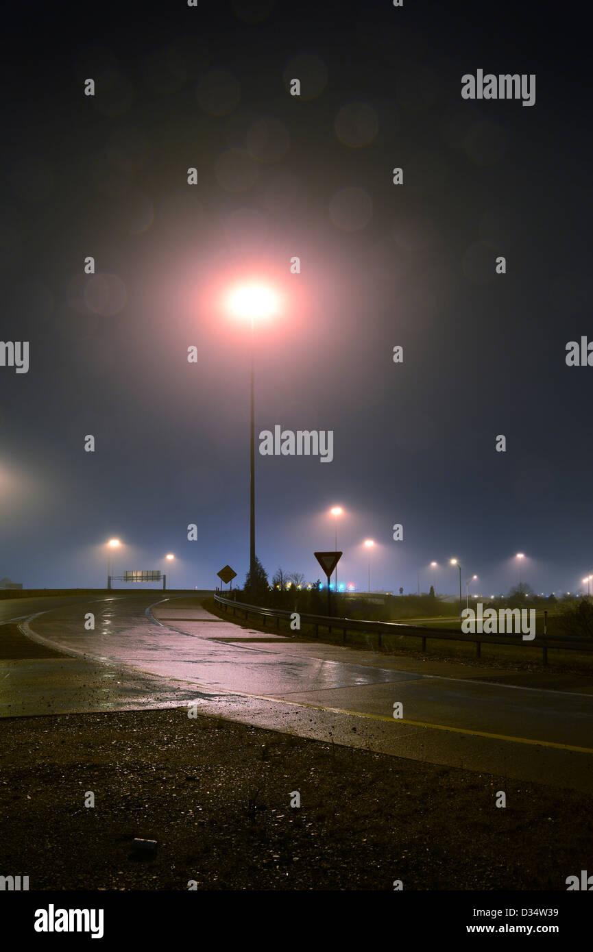 Rampa per autostrada di notte nella nebbia di pioggia con lampada Post Foto Stock