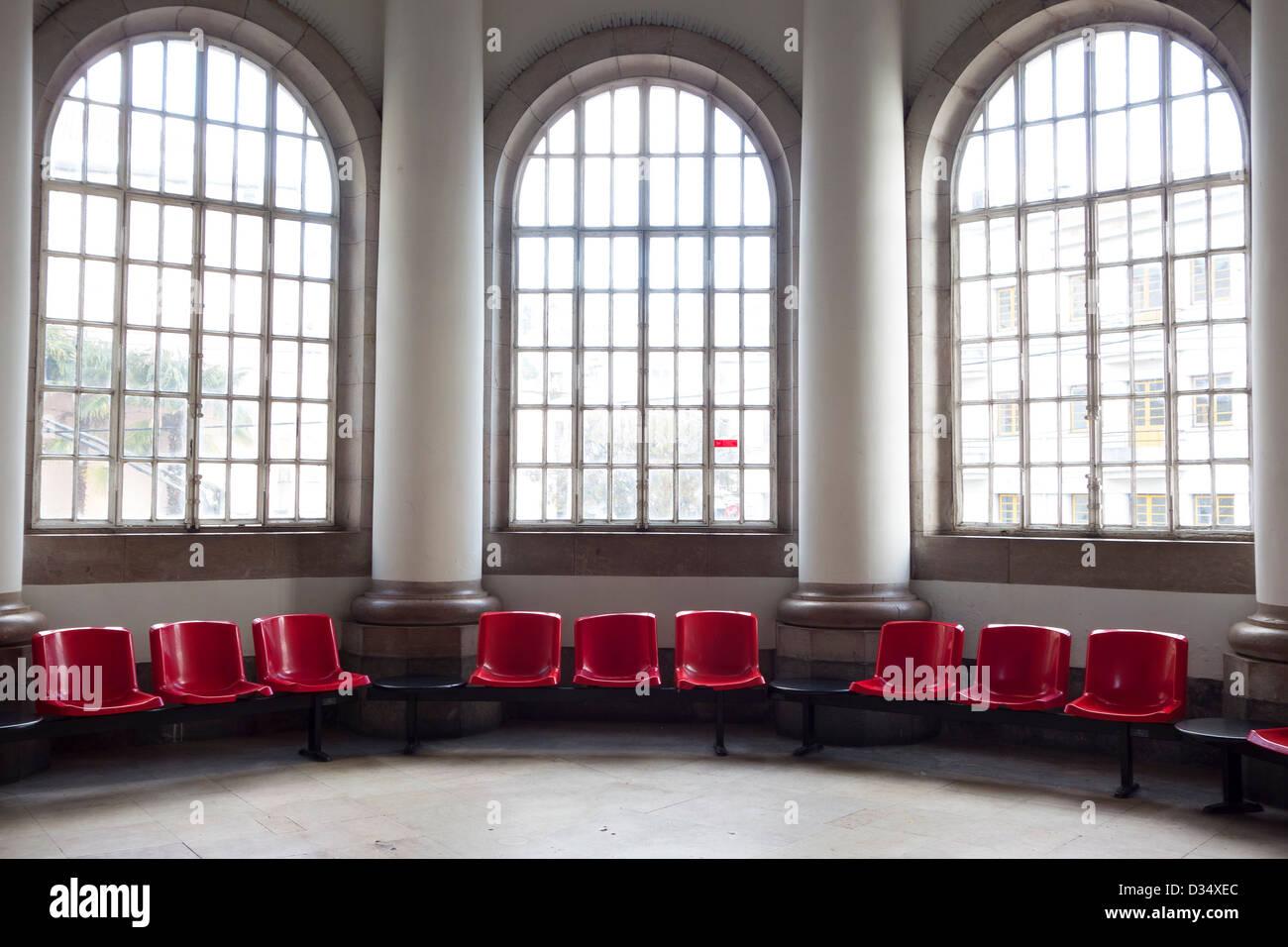 Svuotare il salotto con sedie rosse e grandi finestre Immagini Stock