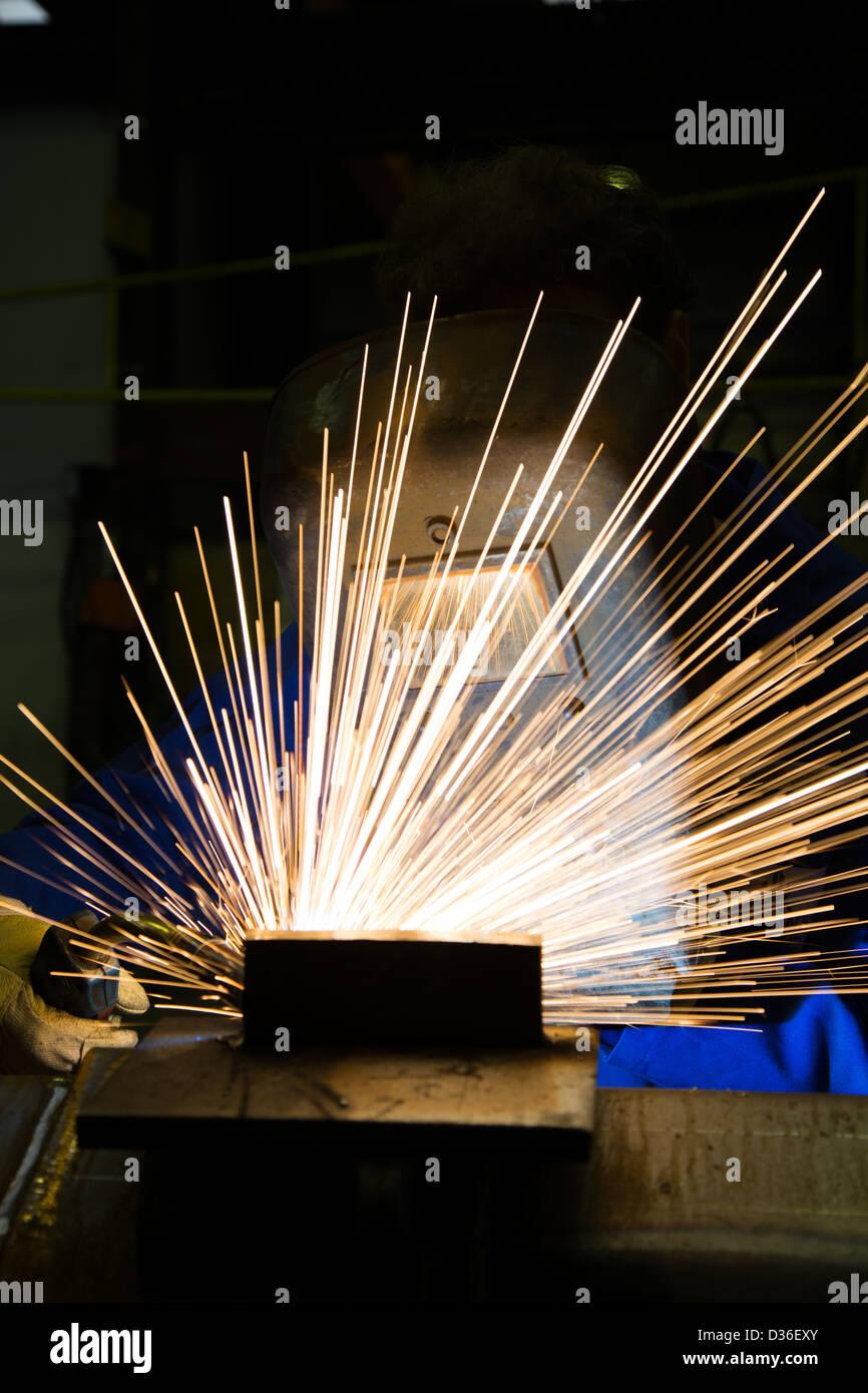 Un lavoratore edile e saldatore è la saldatura di parti in acciaio con un sacco di scintille Immagini Stock