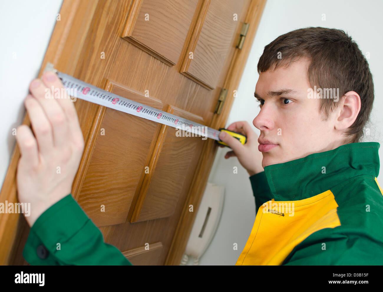 Giovani tuttofare in uniforme lavora con metro a nastro Immagini Stock