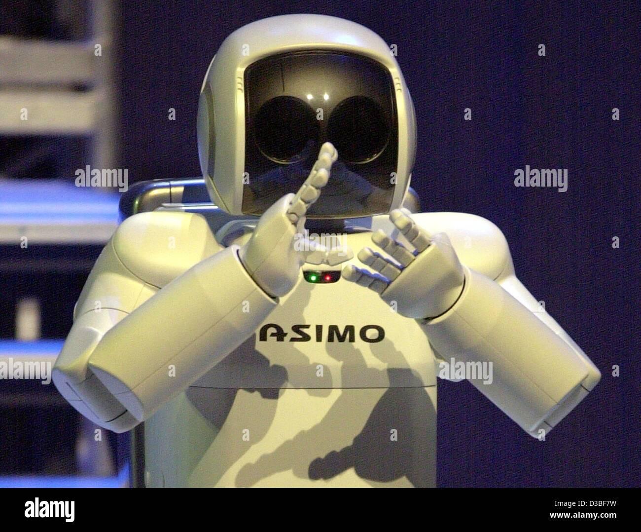 """(Dpa) - L'uomo-robot come 'ASIMO"""" (Advanced passo per una mobilità innovativa) applaude verso Immagini Stock"""