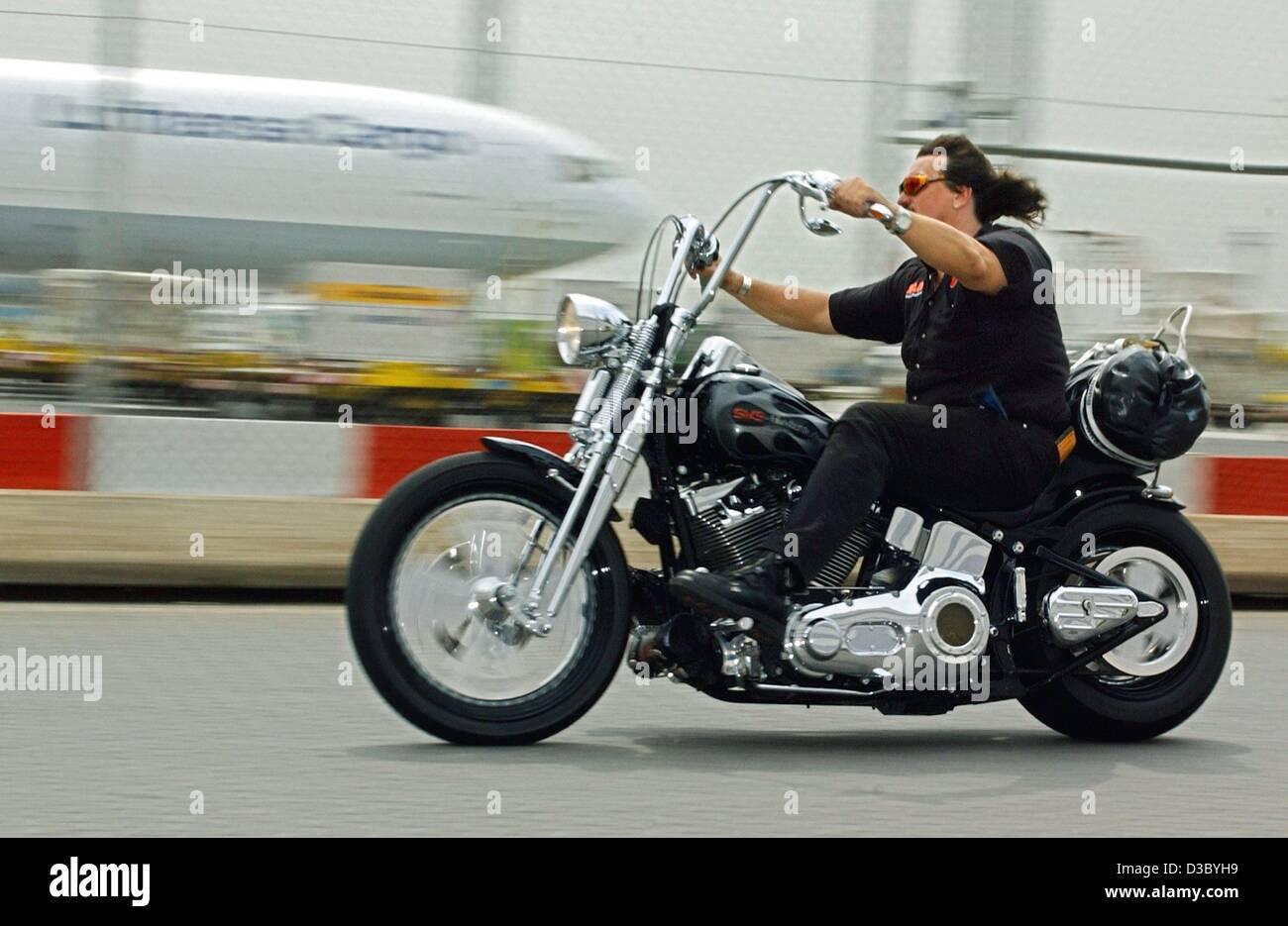 (Dpa) - Un uomo su una Harley Davidson Moto passa su un Lufthansa Cargo Boeing sull'aeroporto di Francoforte, Immagini Stock