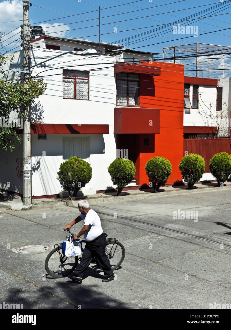 Argento messicano dai capelli uomo ruote bicicletta attraverso il passaggio di intersezione casa moderna con una Immagini Stock
