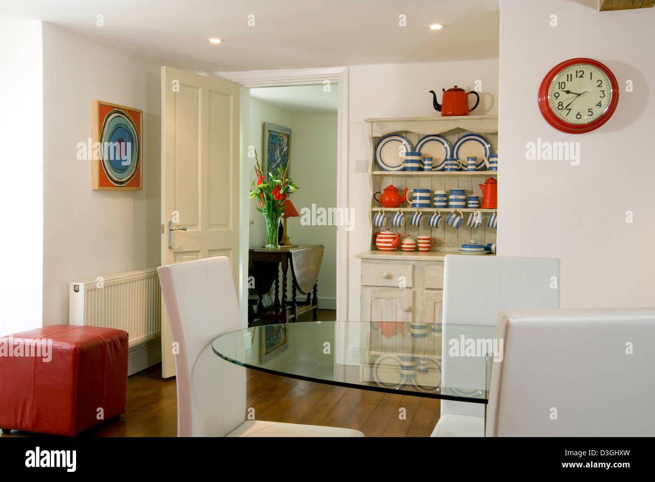 Bianca e luminosa sala da pranzo con particolari rossi colori. Immagini Stock