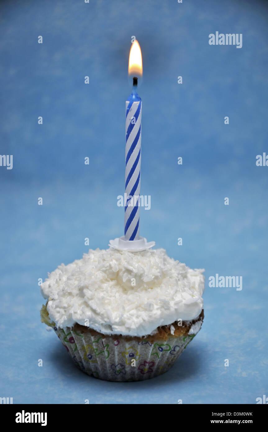La vaniglia tortina con candela accesa sulla parte superiore Immagini Stock