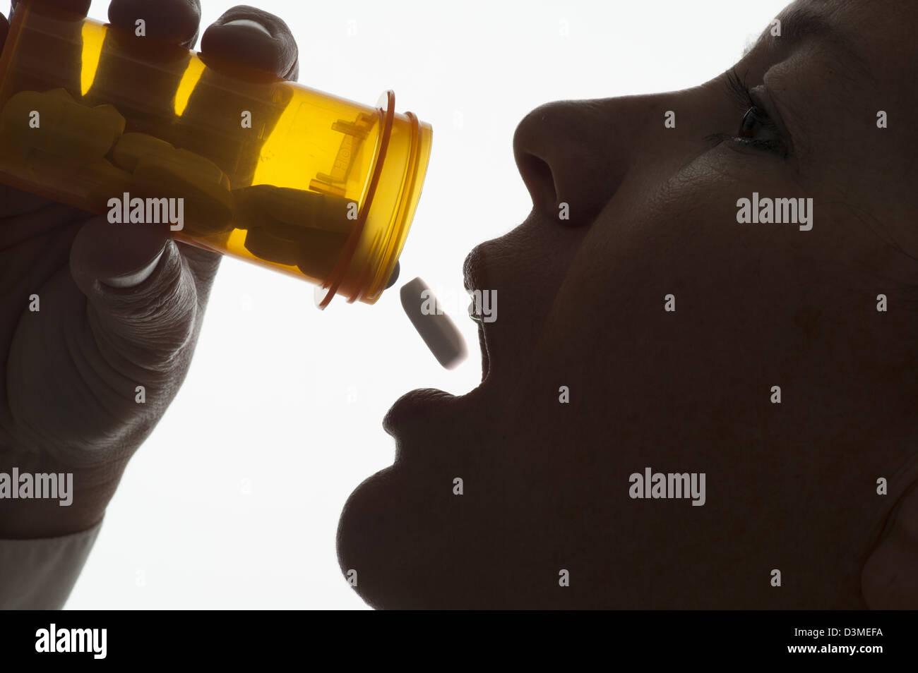 Closeup donna tossing pillola nella sua bocca dipendenza Immagini Stock