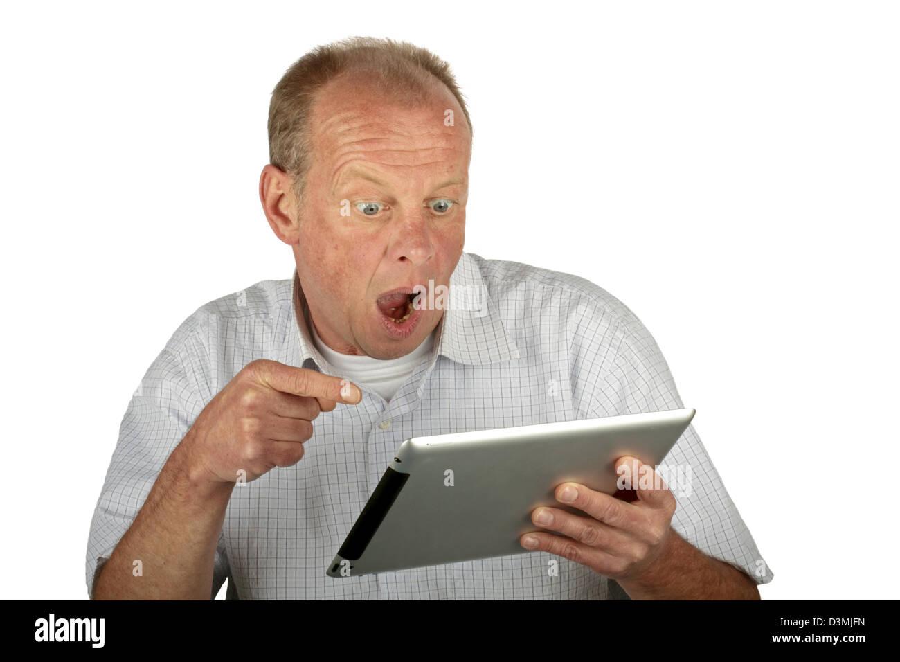 Stupito uomo che guarda il proprio computer tablet Immagini Stock