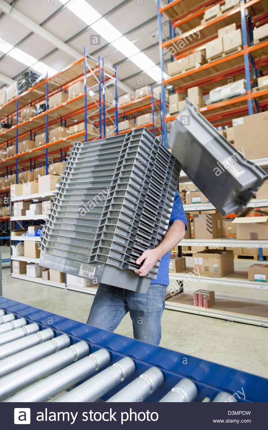Bin cadendo dalla pila portato dal lavoratore nel magazzino di distribuzione Immagini Stock
