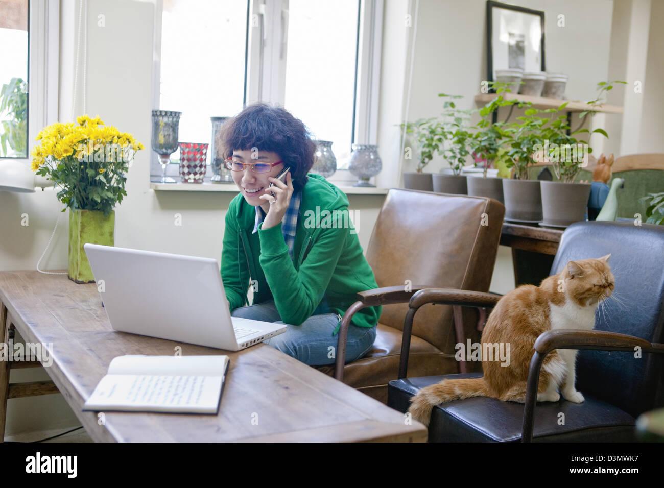 Giovane donna cinese lo Shopping Online mentre si parla al telefono cellulare Foto Stock