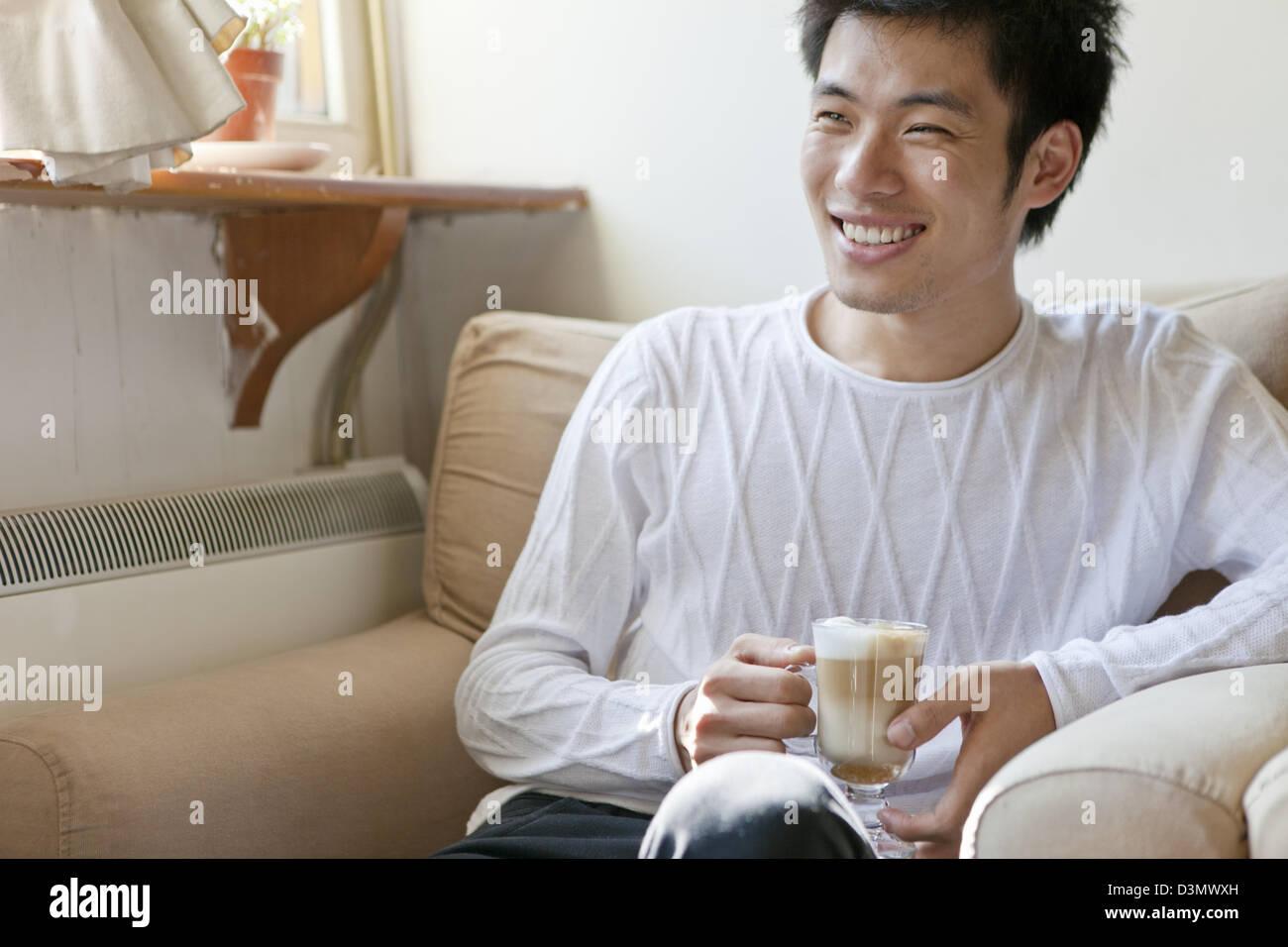 Sorridente giovane uomo cinese in una conversazione di bere il cappuccino Foto Stock