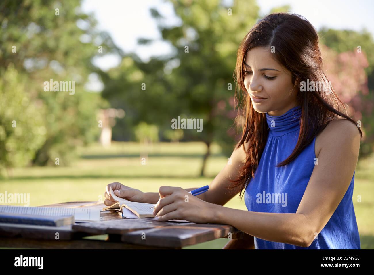 Giovani donne e istruzione, femmina studente di college esame nel parco. Vista laterale, spazio di copia Immagini Stock
