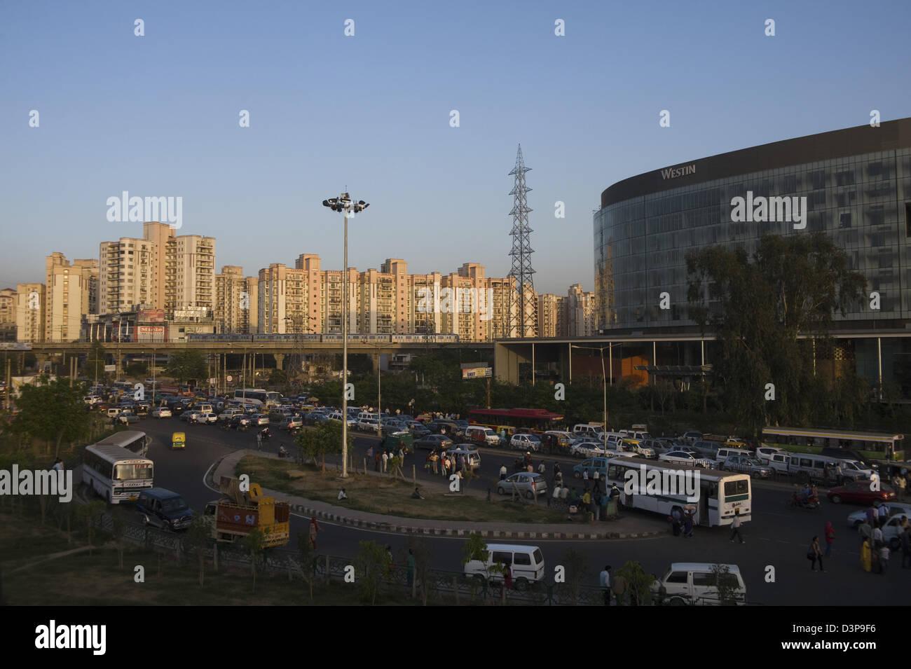 Il traffico su strada con multistoried appartamenti residenziali in background, IFFCO Chowk, Gurgaon, Haryana Immagini Stock