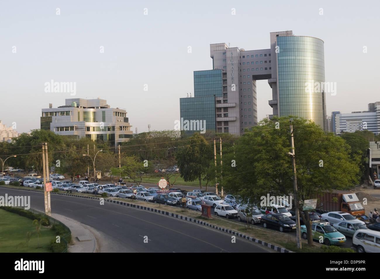 Automobili in attesa ad un semaforo nei pressi di un edificio per uffici, firma torri, Gurgaon, Haryana, India Immagini Stock