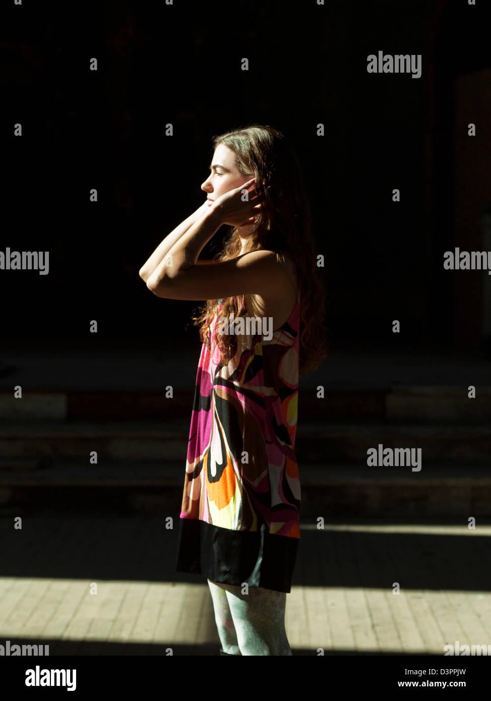 Donna in piedi sotto la luce diretta del sole Immagini Stock