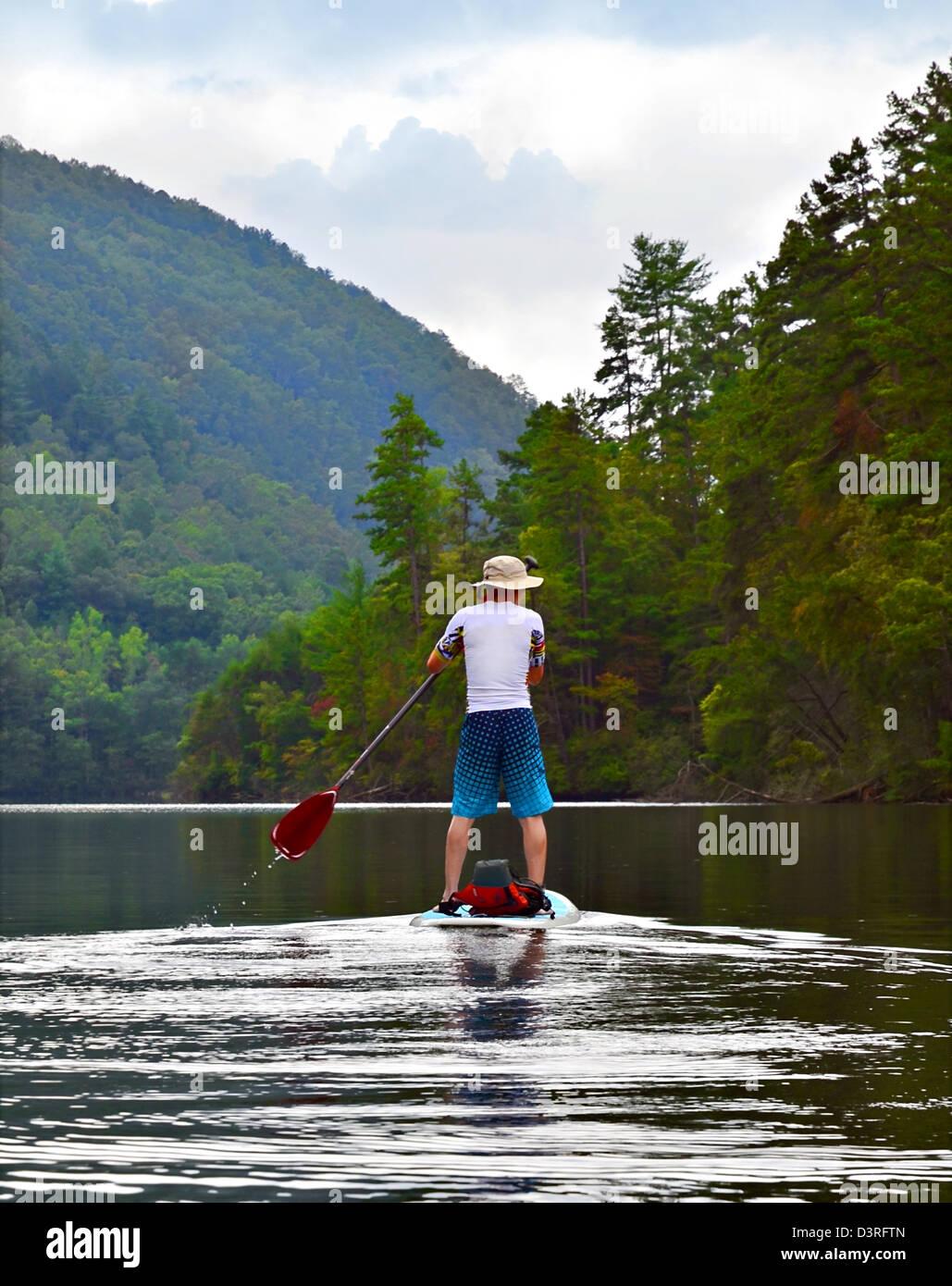 Un uomo su un paddleboard in un lago di montagna. Immagini Stock