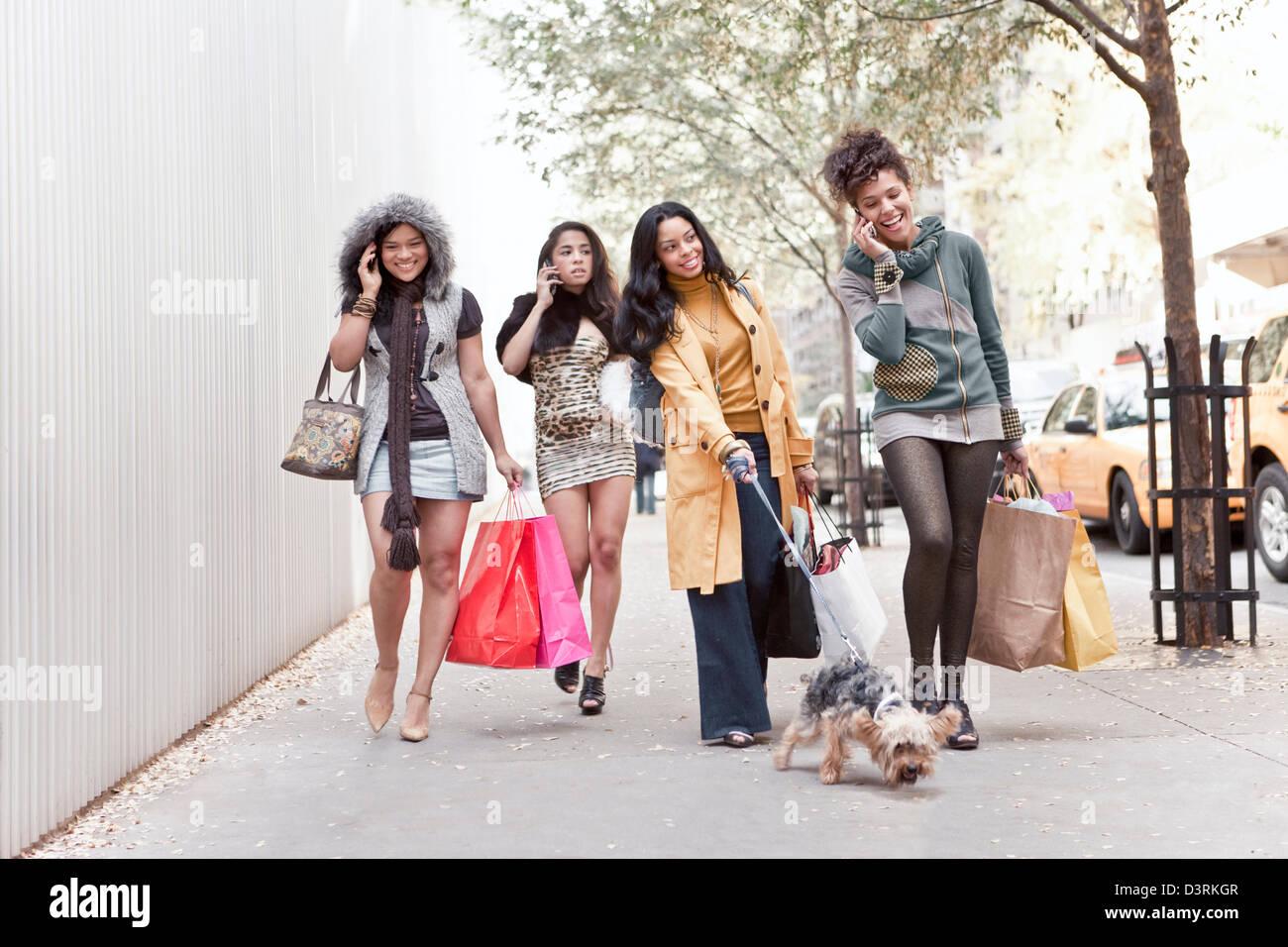 Il gruppo di donne amici parlando al cellulare mentre si cammina Foto Stock