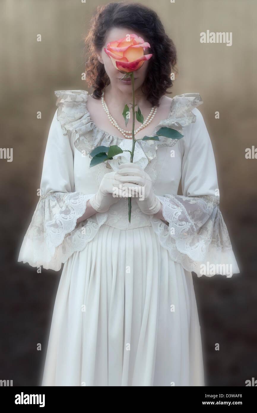 Una donna in un abito vittoriano è in possesso di una rosa di fronte il suo volto Immagini Stock