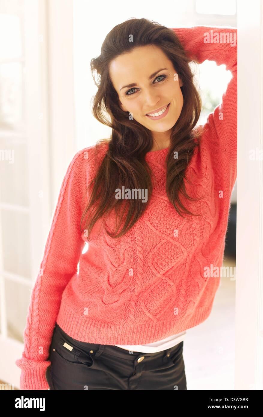 Ritratto di una allegra donna coperta con un maglione in piedi dentro la sua casa Immagini Stock