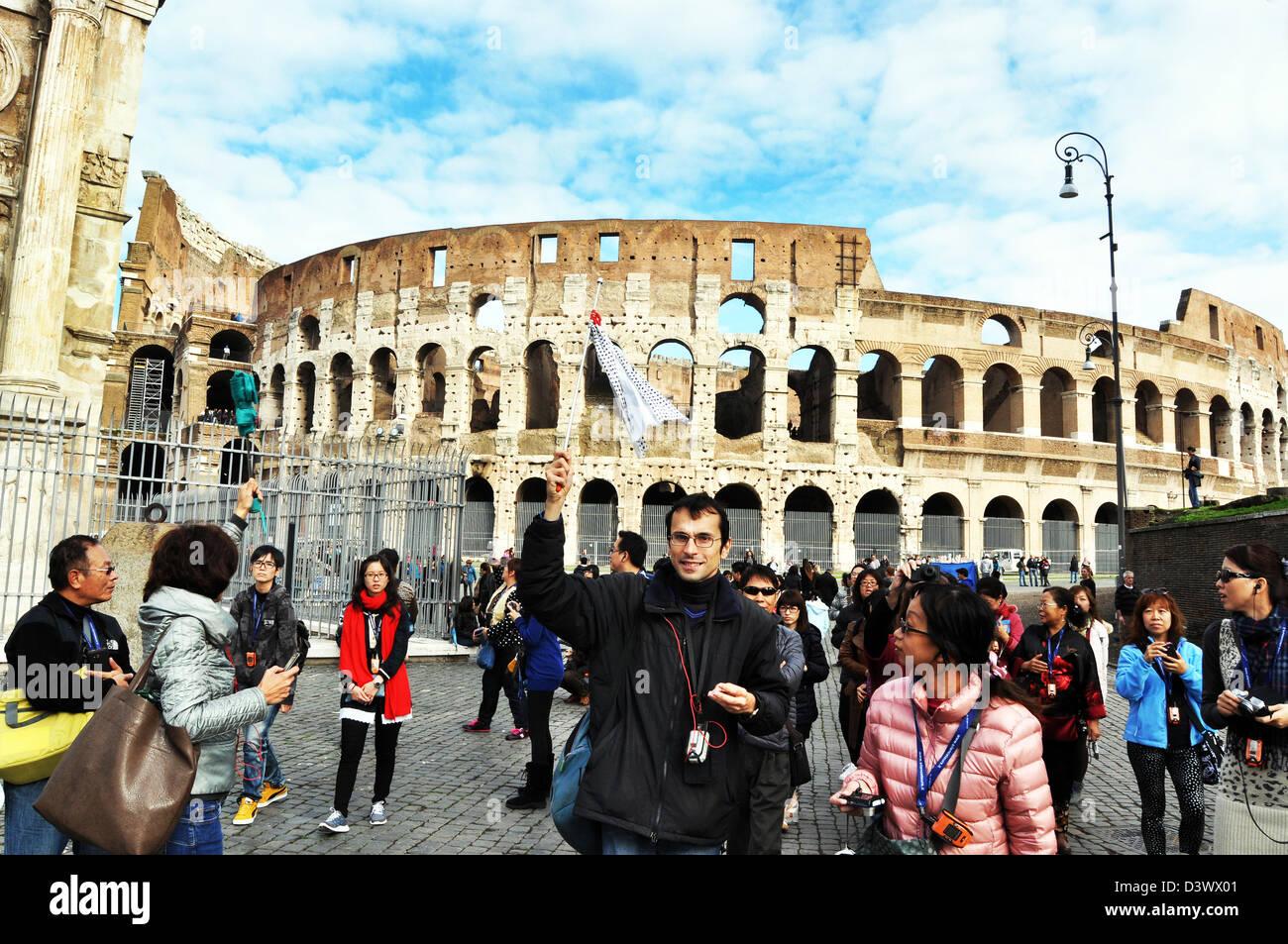 I turisti giapponesi vengono arrotondati da una guida locale, Colosseo Roma Italia Immagini Stock