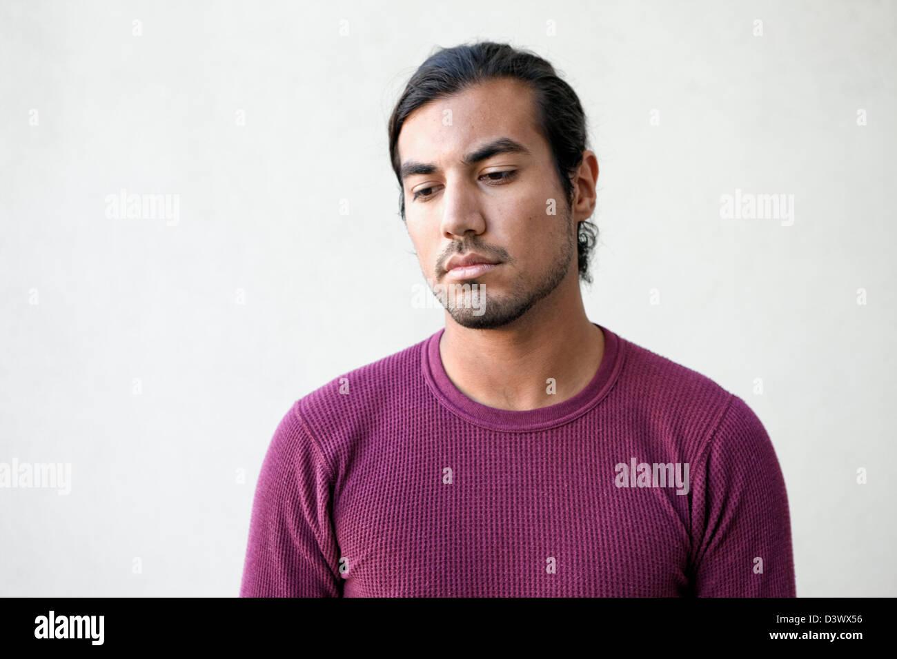 Ritratto di triste e depresso i giovani adulti messicano-american maschio nel pensiero profondo Foto Stock