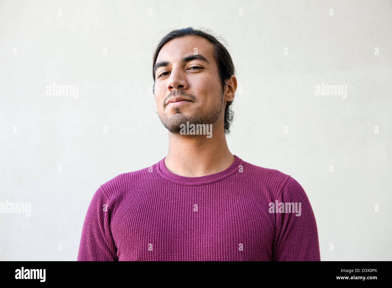 Ritratto di giovane adulto con i capelli lunghi messicano-american maschio con espressione di semi-sorriso, dubbio e giocosità Foto Stock
