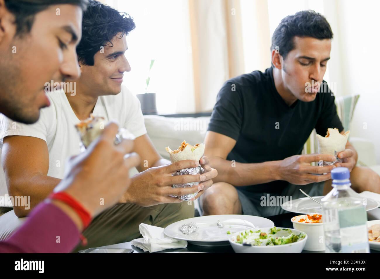Ispano-americana uomini di mangiare Burrito, cibo messicano in salotto Foto Stock
