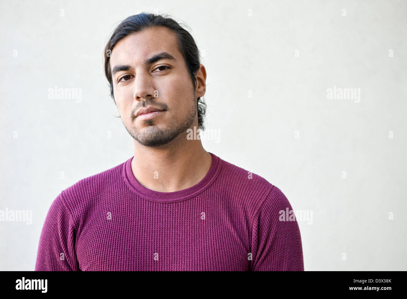 Ingenui e fiduciosi Ritratto di giovane dai lunghi capelli Mexican-American adulto maschio Foto Stock