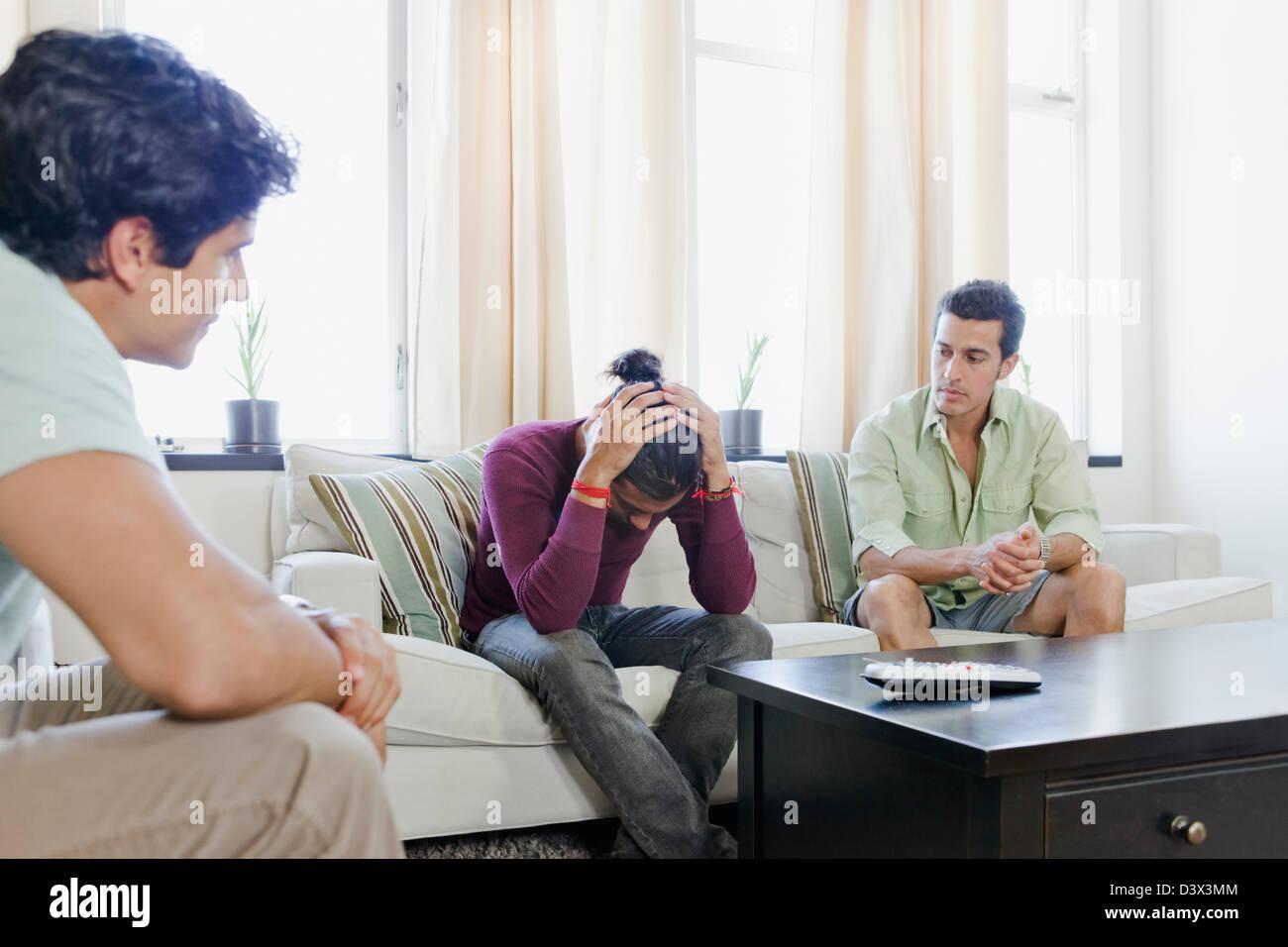 Uomini Mexican-American aiutando un amico a risolvere problemi personali mediante intervento di gruppo Foto Stock