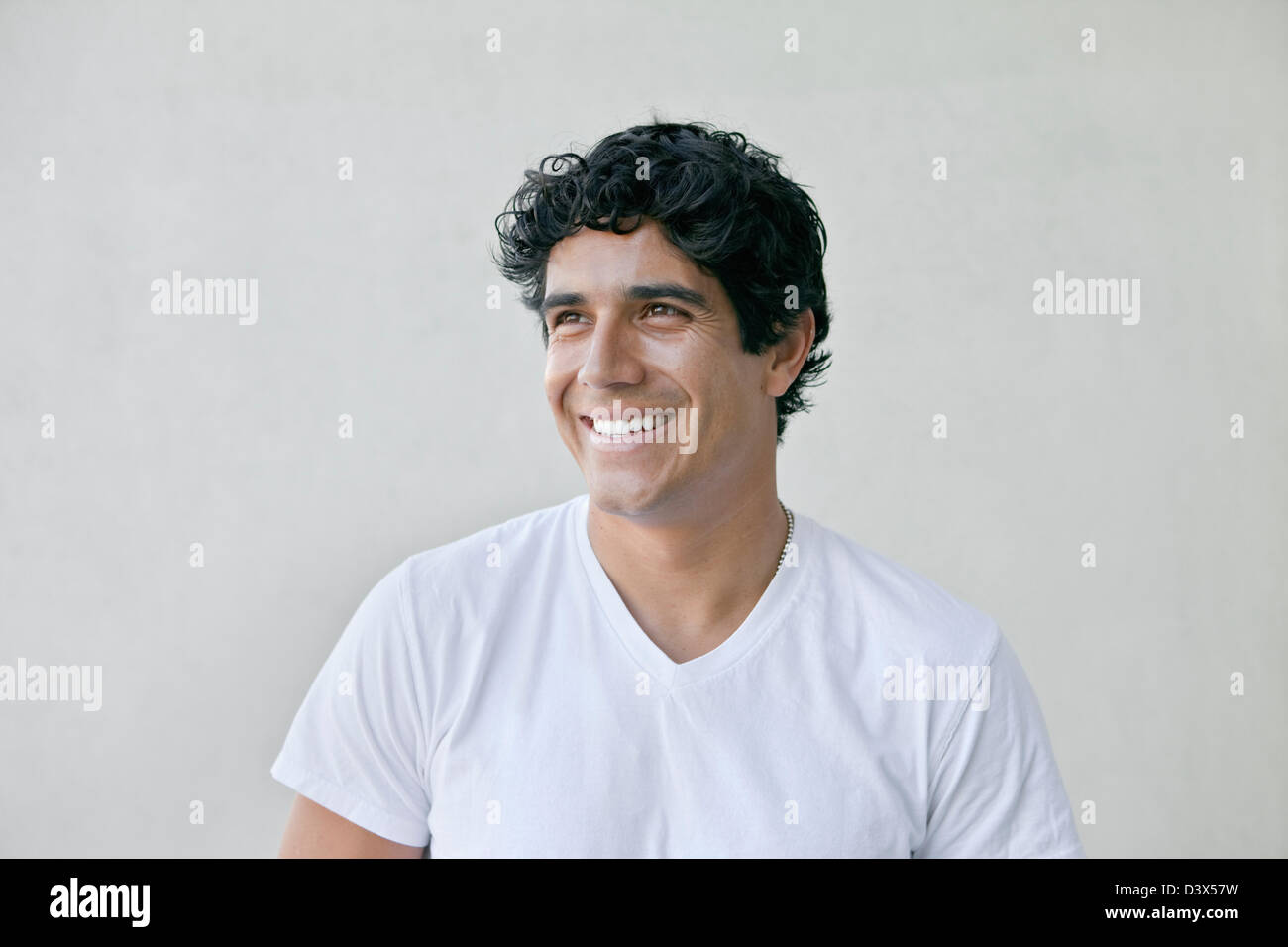 Sorridente Ritratto di giovane adulto messicano-americana indossa maschio bianco semplice t-shirt e khakis Foto Stock