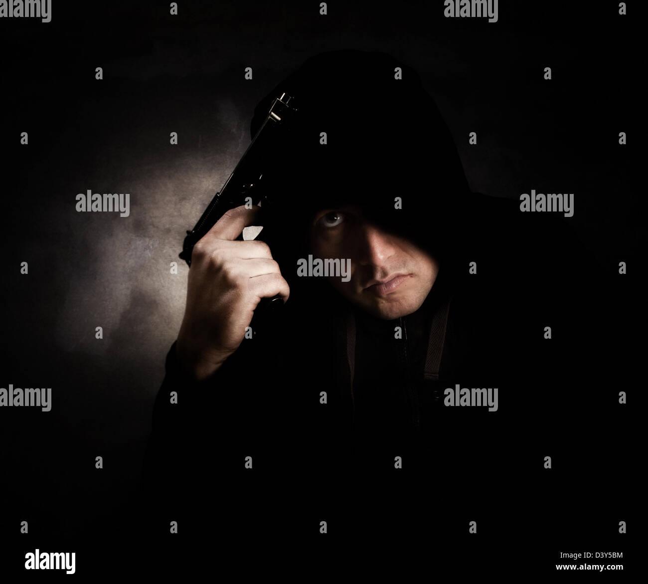 Membro della gang che indossa un nero felpa con cappuccio in possesso di una pistola con un espressione arrabbiato.La Immagini Stock