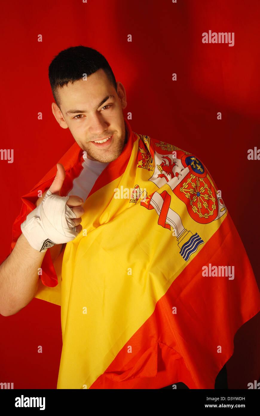 Giovane uomo avvolto in una bandiera spagnola, sorridente e pollice in alto. Immagini Stock