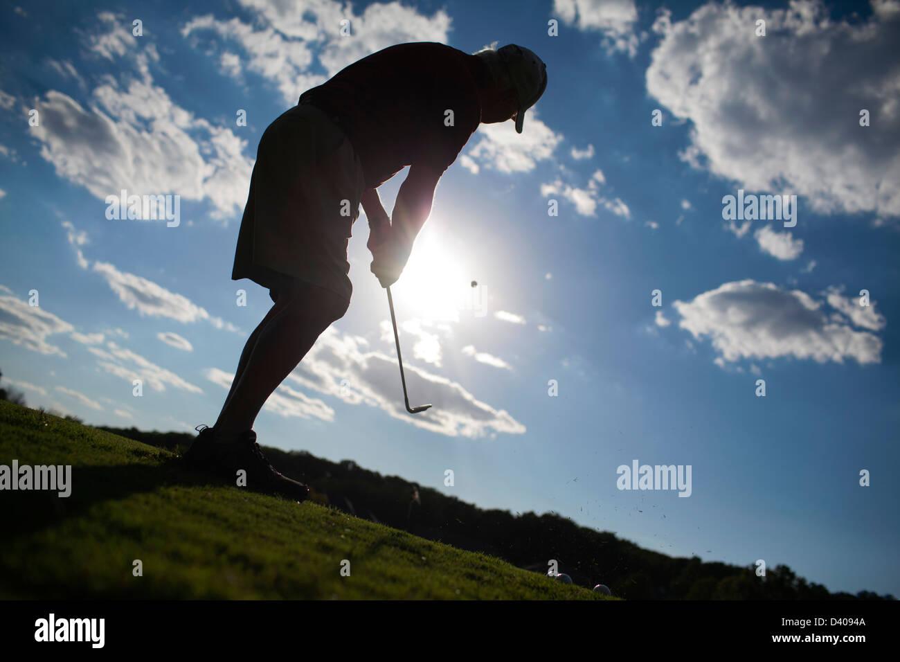 Un golfista senior piazzole su un verde a un campo pratica da golf gamma. Immagini Stock