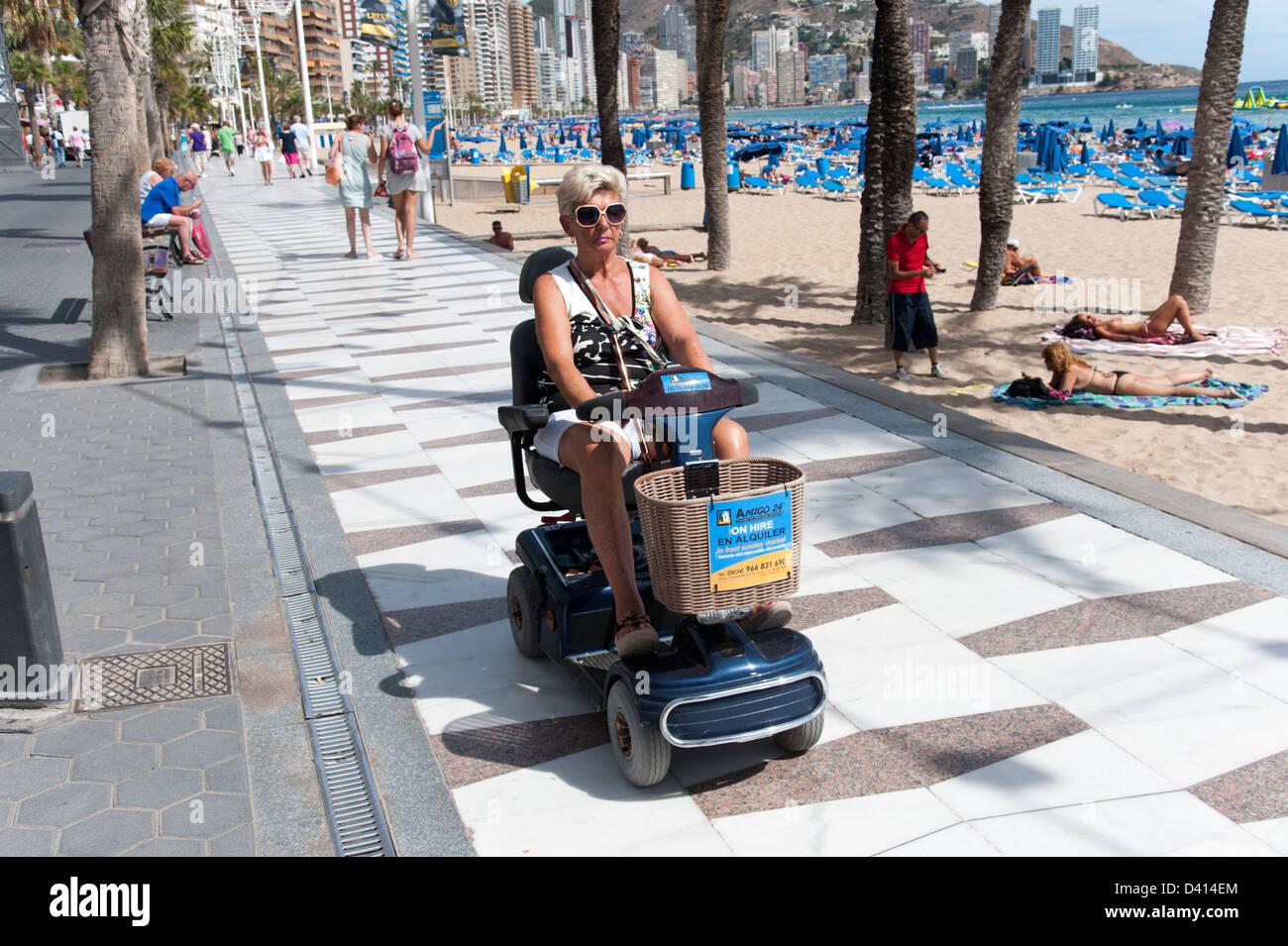 Donna che utilizza noleggiato scooter di mobilità sul lungomare, Benidorm, Costa Blanca, Spagna Immagini Stock