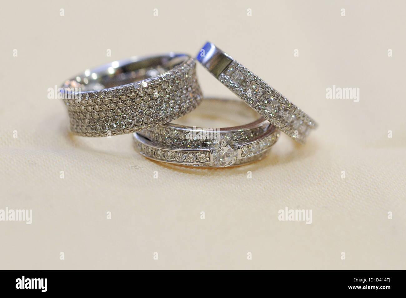 Tre oro bianco anelli di diamante su uno sfondo color crema Immagini Stock