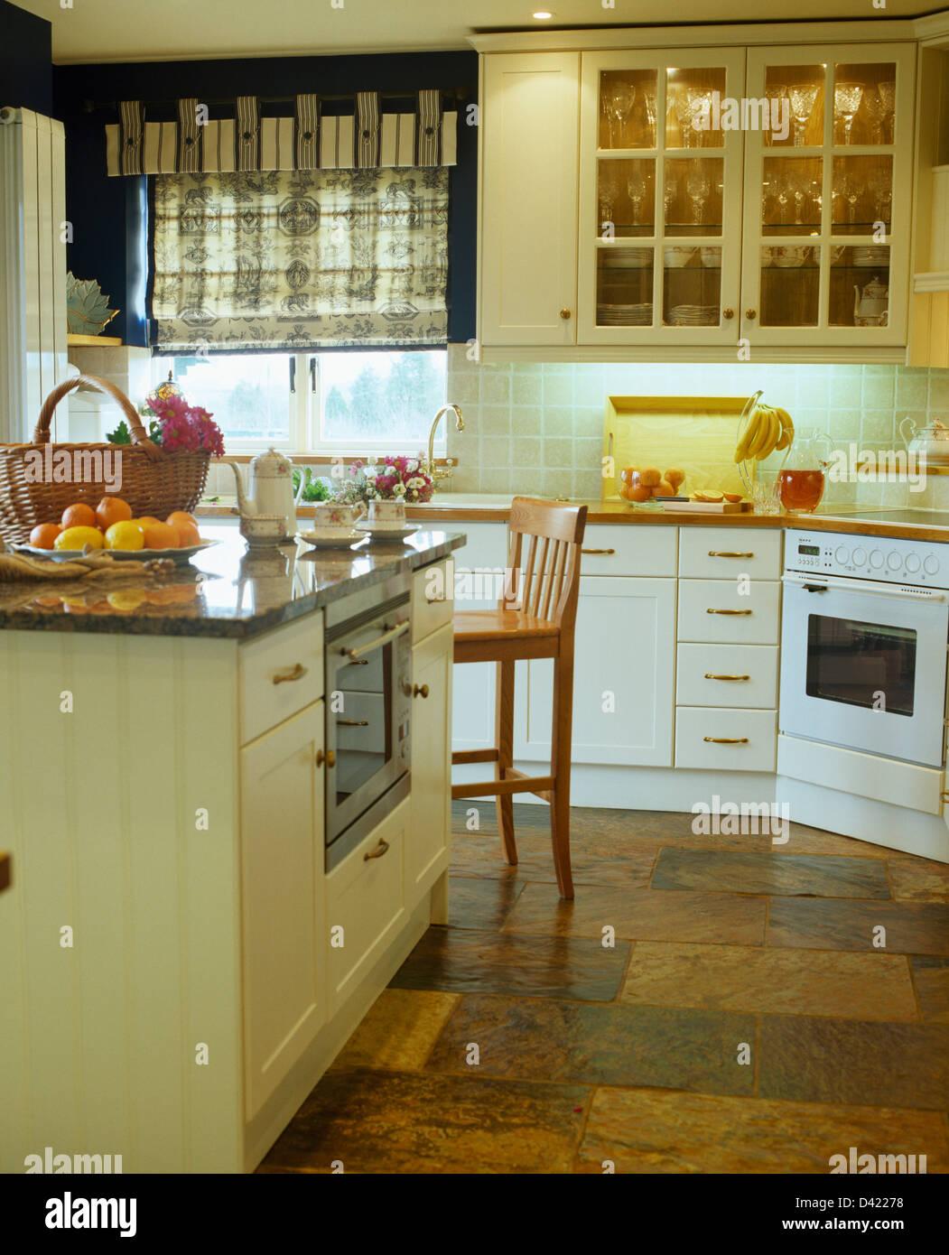 Unità di isola e pavimento di ardesia in cucina di paese con ciechi ...