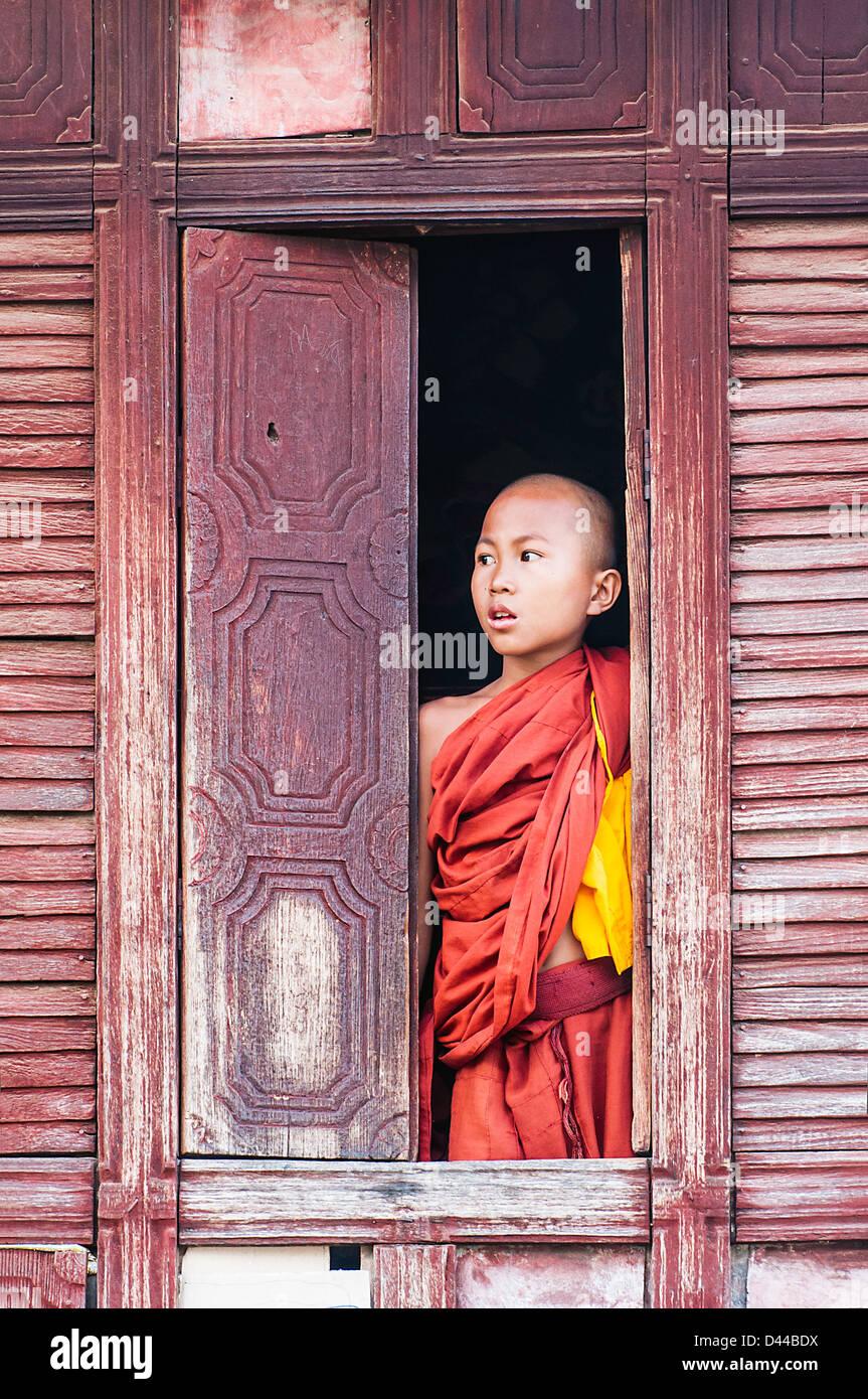 Buddista birmano monaco novizio guardando fuori della finestra, Nyaungshwe, o MYANMAR Birmania Immagini Stock
