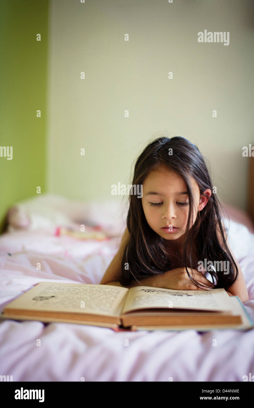 La ragazza si trova nel letto del libro di lettura Immagini Stock