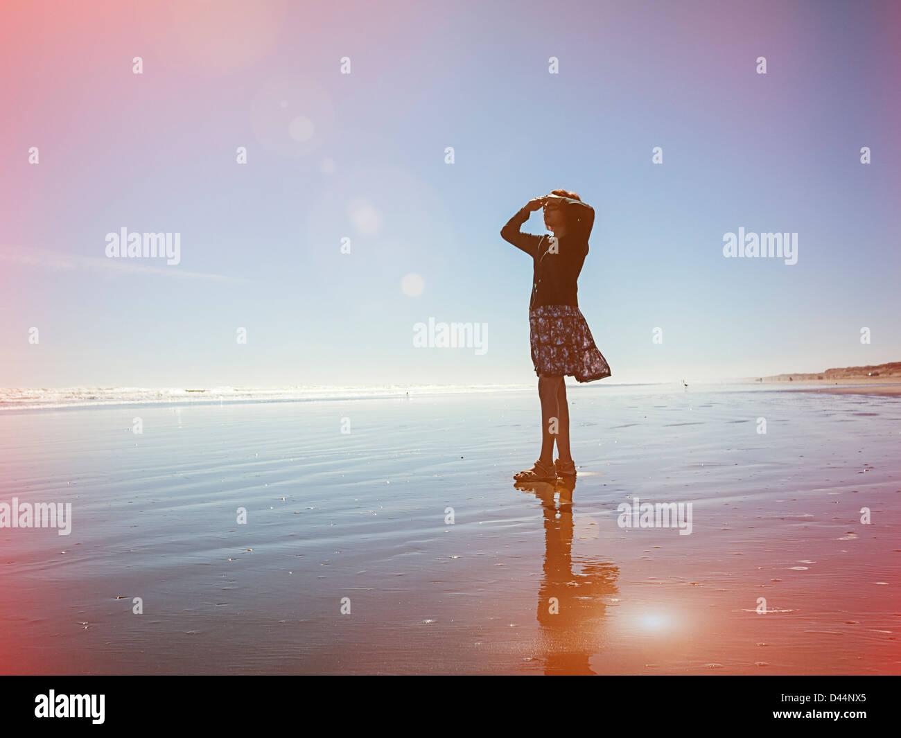 Perdite della luce, donna guarda al mare, Nuova Zelanda. Immagini Stock