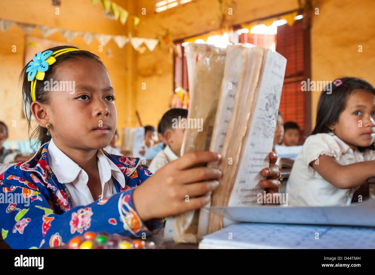 Ragazza giovane nella scuola prestando attenzione all'insegnante di una Cambogia Cambogia scuola Immagini Stock