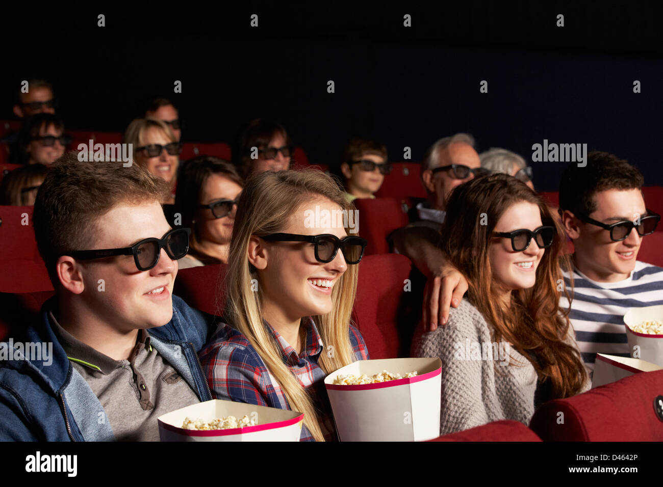 Gruppo di amici adolescenti guardando film 3D nei cinema Immagini Stock