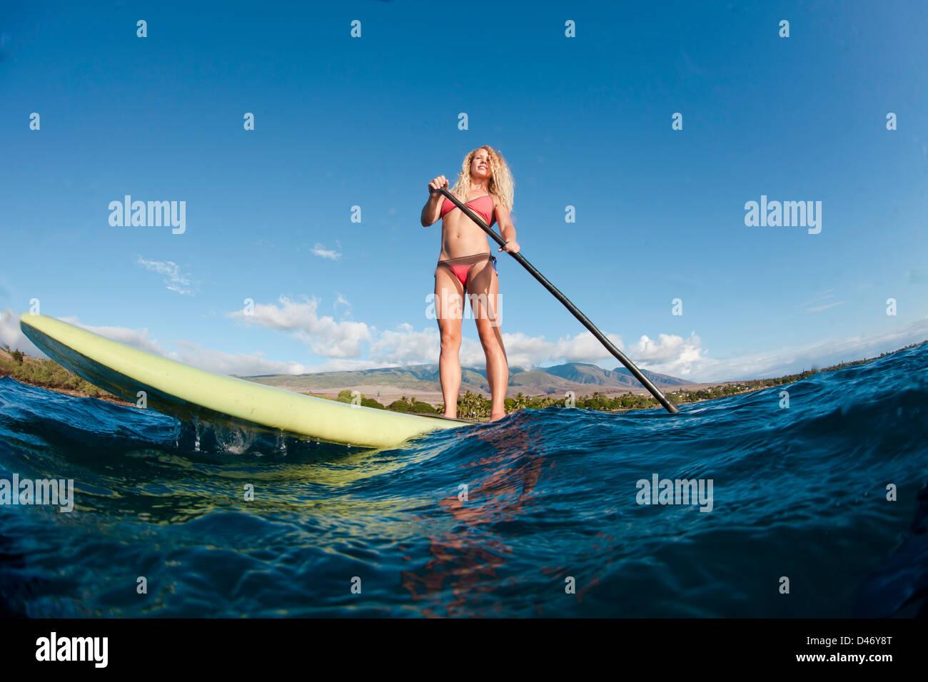 Istruttori di Surf Tara Angioletti su uno stand up paddle board off Bearch canoa, Maui. Hawaii. Immagini Stock