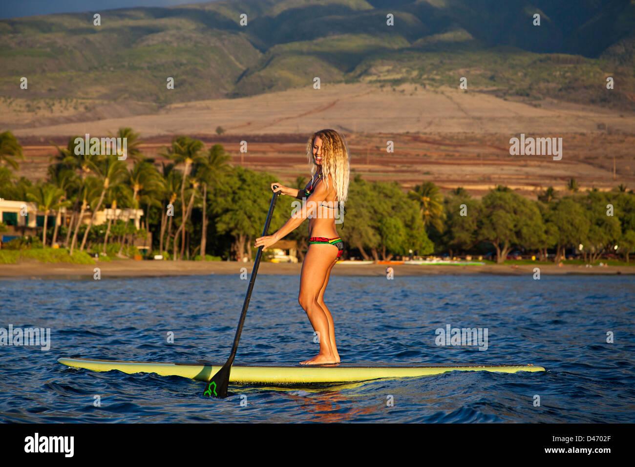 Istruttori di Surf Tara Angioletti su uno stand up paddle board off spiaggia di Canoa, Maui. Hawaii. Immagine modello Foto Stock
