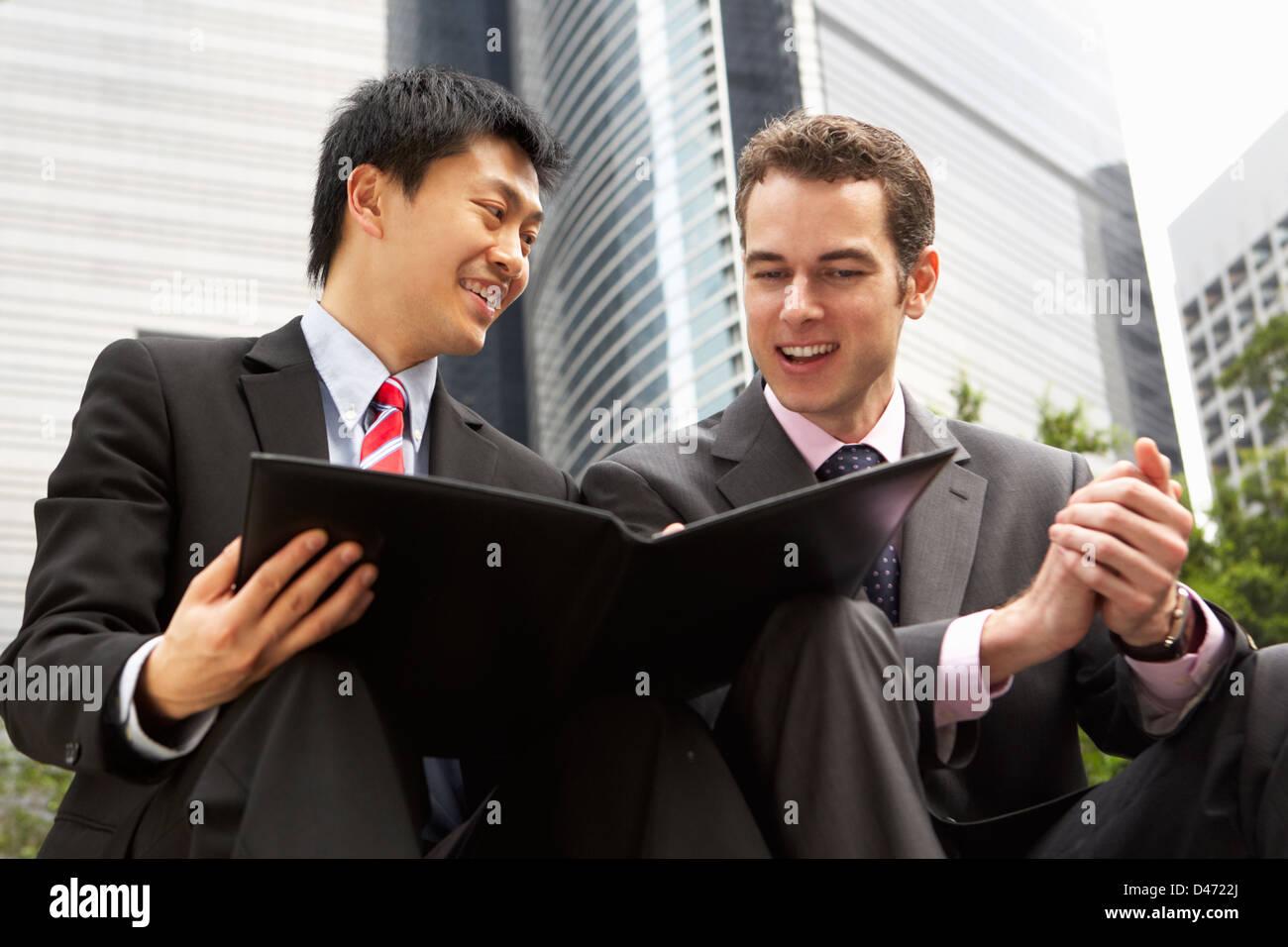 Due imprenditori per discutere il documento al di fuori ufficio Foto Stock
