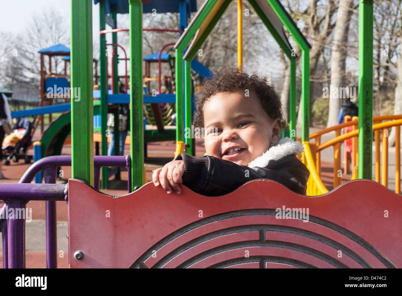 Razza mista toddler baby sorridente e giocando sul telaio di arrampicata in una giornata di sole indossando giacca aviator Foto Stock