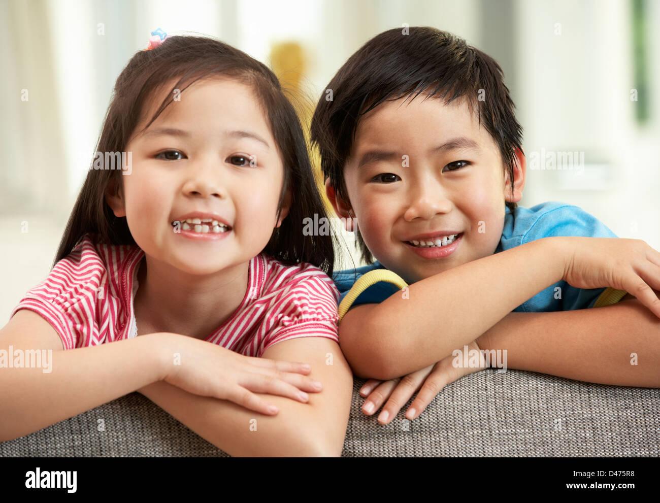 Due bambini cinesi rilassante sul divano di casa Immagini Stock