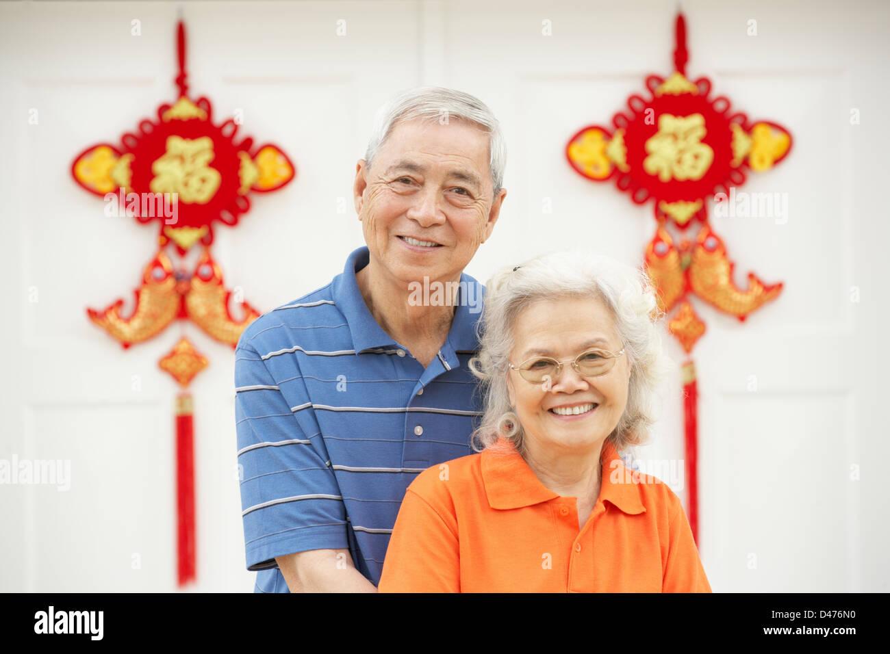 Senior coppia cinese al di fuori di casa decorata con accogliente Feng Shui banner Immagini Stock