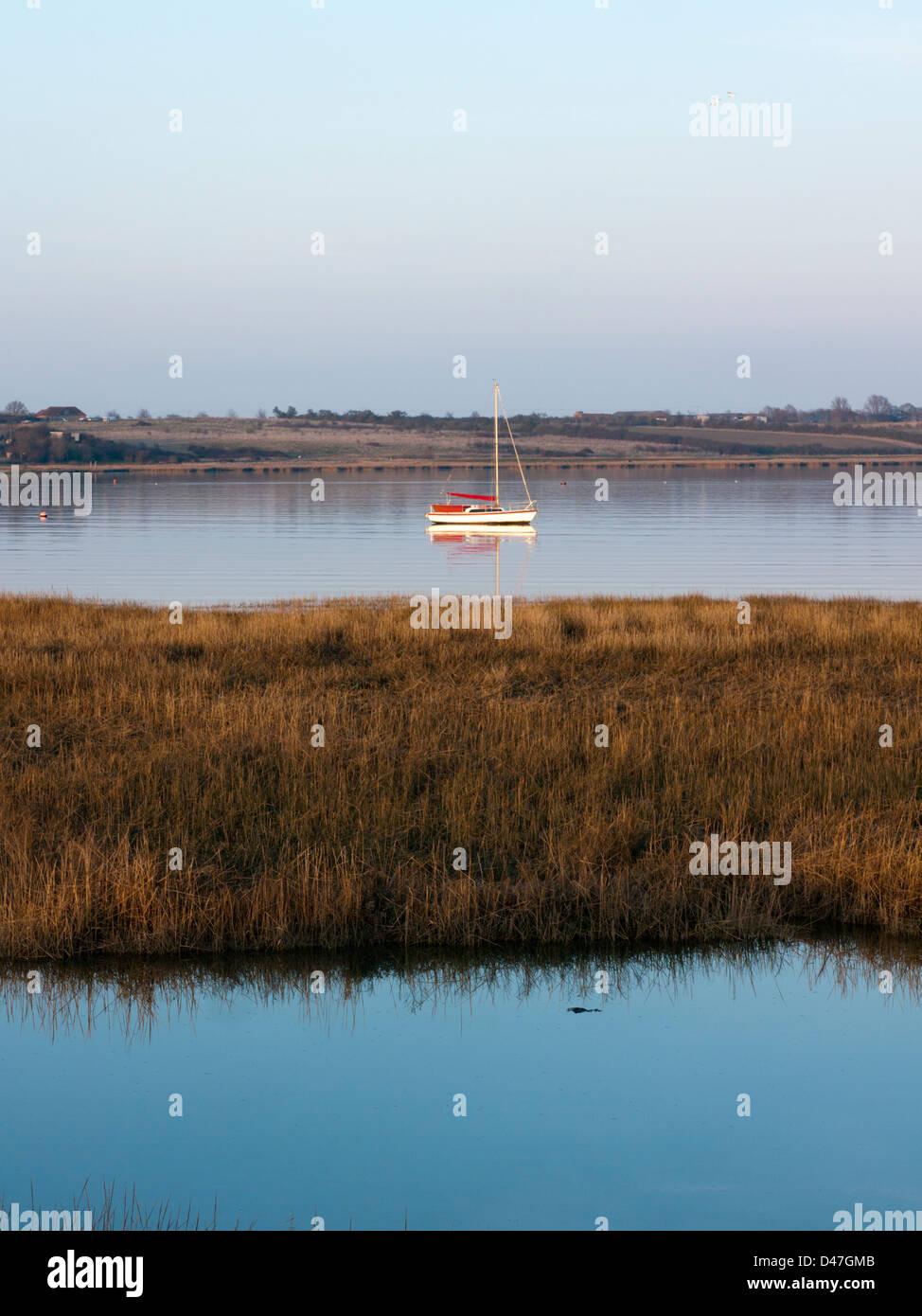Barca a vela ormeggiata sulle calme acque del Swale Foto Stock