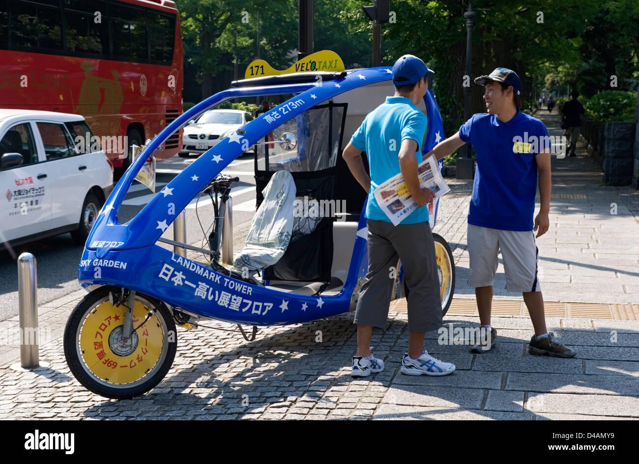 Un velo taxi driver attende per un cliente in Yamashita Koen Park sul lungomare della città di Yokohama, Giappone. Immagini Stock
